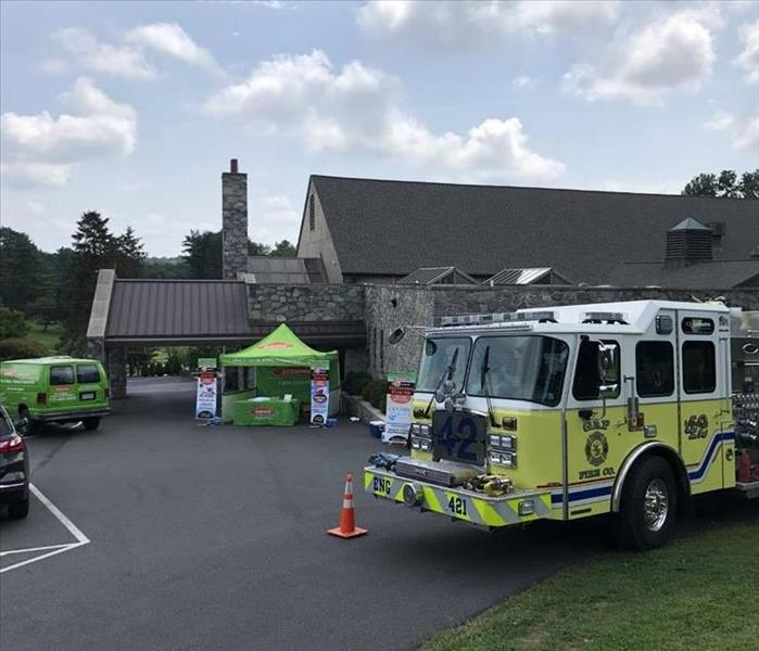 A Servpro van, Servpro tent, and a firetruck outside of a building