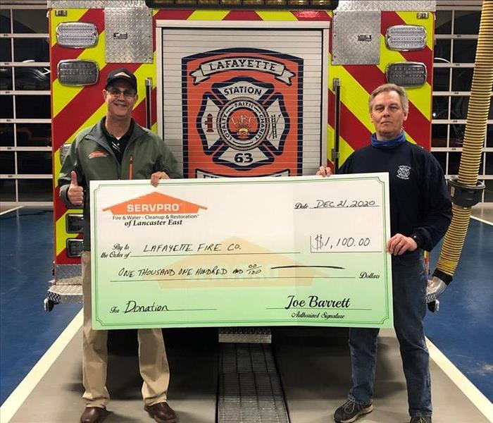 SERVPRO sales manager and fire company employee holding a large display check board