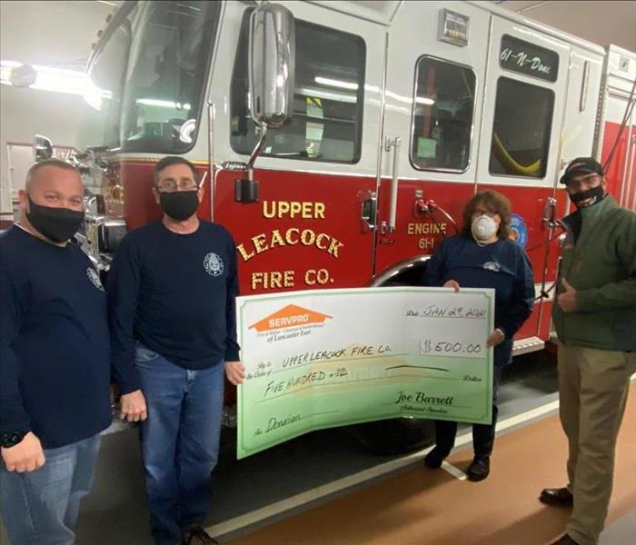 SERVPRO sales manager with members of a fire department holding a large check display board with a fire truck