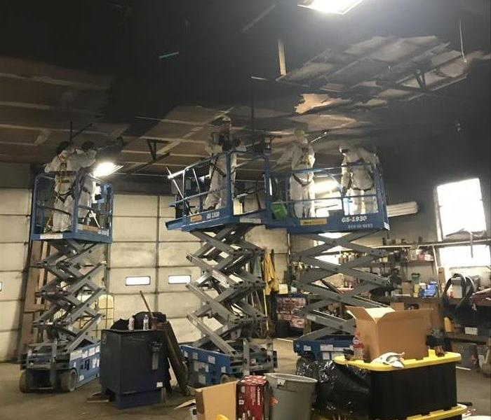 Technicians on lifts cleaning soot off of the ceiling at an automatic shop