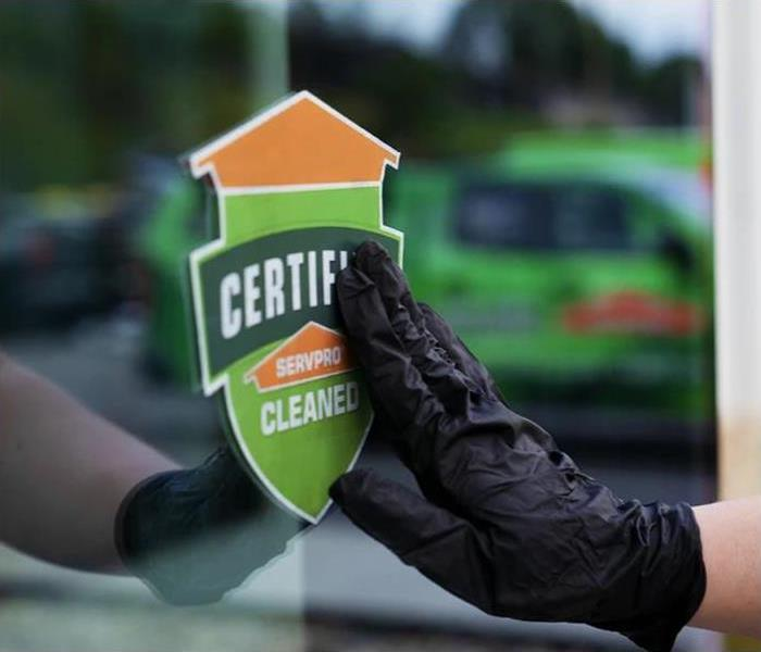 "Hand with a latex glove on touching a ""Certified: SERVPRO Cleaned"" sticker on a window"
